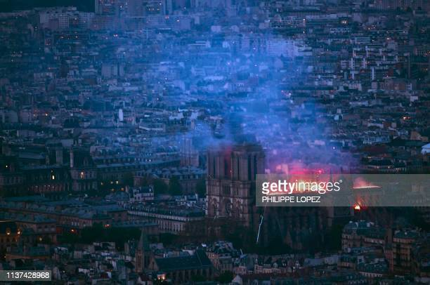 TOPSHOT This general view taken from Montparnasse Tower shows flames and smoke as they billow from the roof at NotreDame Cathedral in Paris on April...
