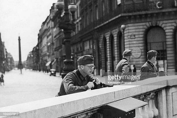 This German soldier is standing against the parapet of the exit of the underground station of Opera Behind him is the Place Vendôme