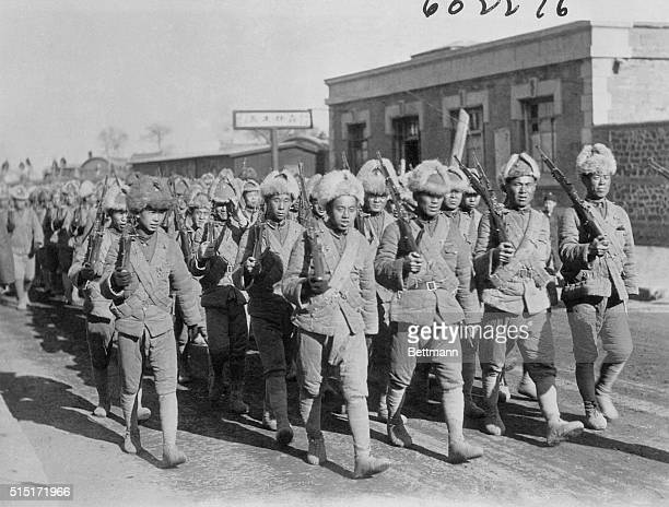 This glimpse of a battalion of Mukden forces marching to the advance posts at Chinchow is one of the first actual photographs to be made of the...