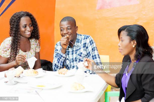 this group of friends sitting in a restaurant sharing  a meal together in joy. - femme ivoirienne photos et images de collection