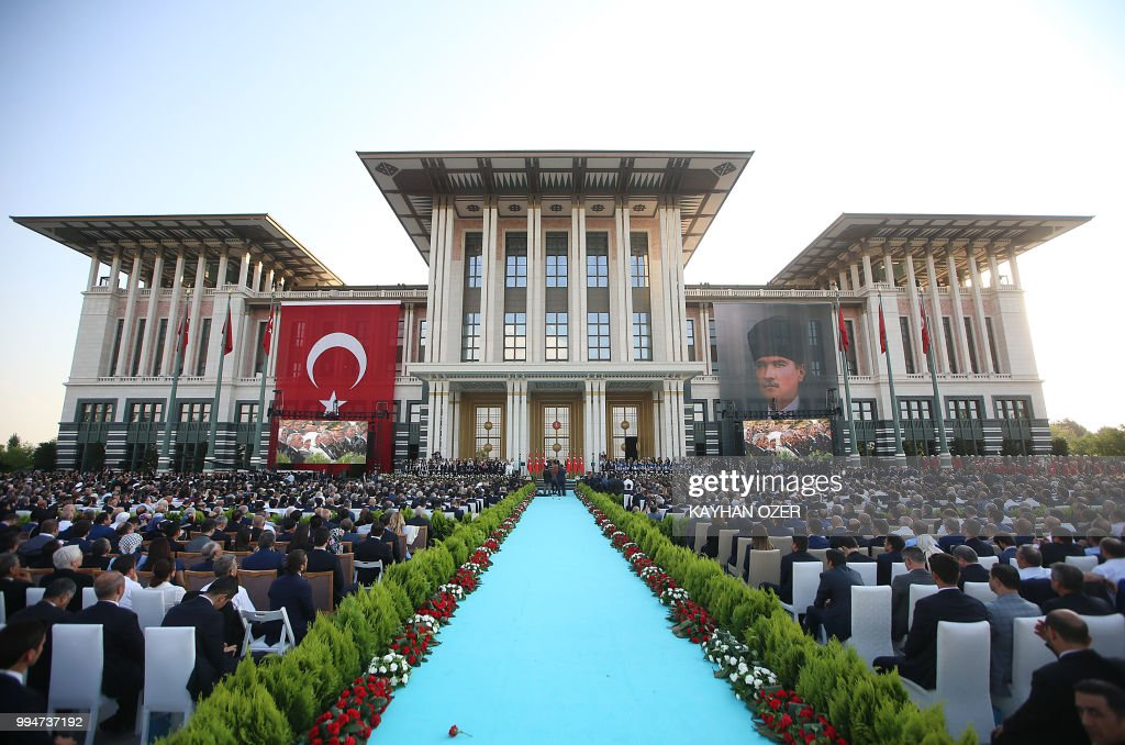 This hand out picture taken and released on July 9, 2018 by Turkish President Office shows people listening Turkish President Recep Tayyip Erdogan (unseen) delivering a speech at the Presidential Complex in Ankara. - Erdogan was sworn in for his second term as head of state on July 9, taking on greater powers than any Turkish leader for decades under a new system condemned by opponents as a one-man regime. Erdogan, who has transformed Turkey in 15 years of rule by allowing Islam a greater role in public life and boosting its international stature, took his oath in parliament for a five-year term after his June election victory.