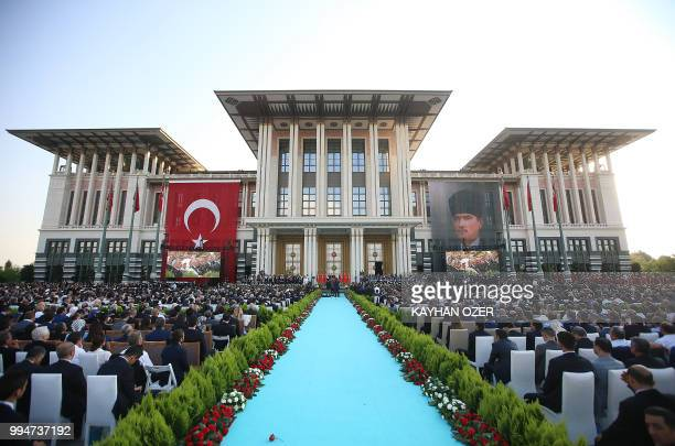 This hand out picture taken and released on July 9 2018 by Turkish President Office shows people listening Turkish President Recep Tayyip Erdogan...