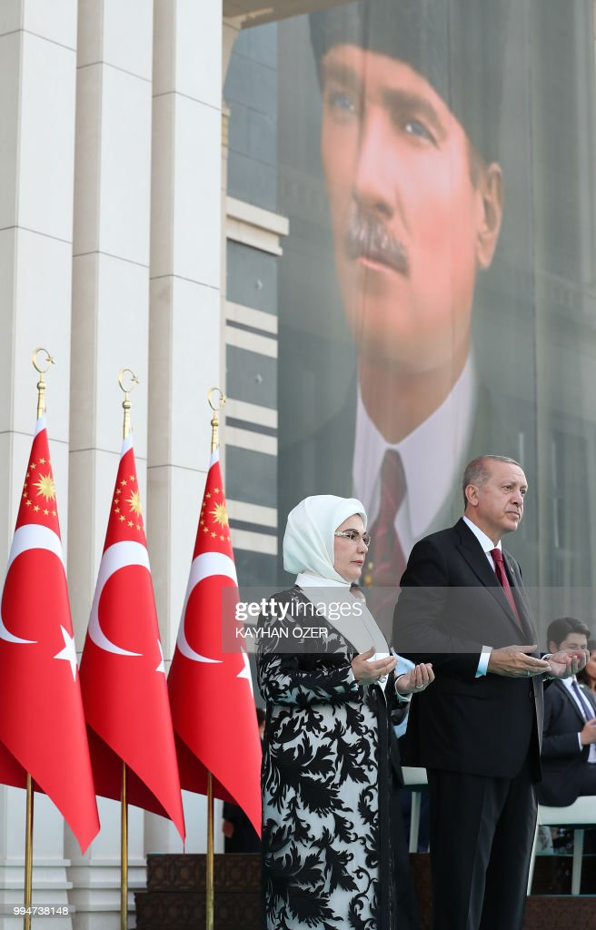 This hand out picture taken and released on July 9, 2018 by Turkish President Office shows Turkish President Recep Tayyip Erdogan praying with his wife Emine Erdogan, during a ceremony at the Presidential Complex in Ankara. - Erdogan was sworn in for his second term as head of state on July 9, taking on greater powers than any Turkish leader for decades under a new system condemned by opponents as a one-man regime. Erdogan, who has transformed Turkey in 15 years of rule by allowing Islam a greater role in public life and boosting its international stature, took his oath in parliament for a five-year term after his June election victory.