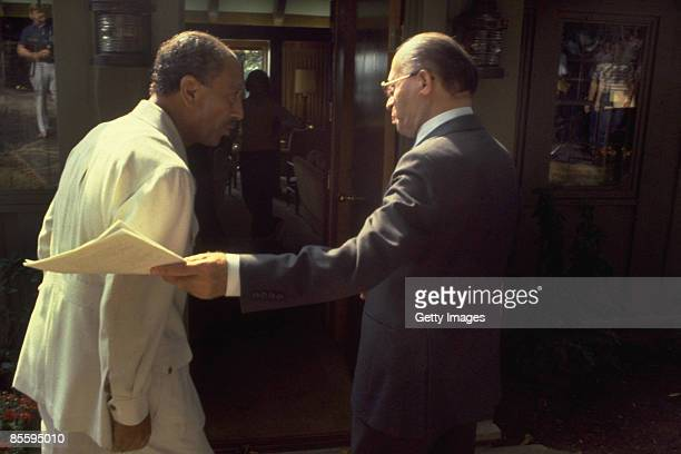 This handout file photo provided by the Israeli Government Press Office on March 25 shows Israeli Prime Minister Menahem Begin inviting Egyptian...