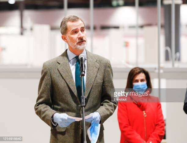 This handout image provided by the Spanish Royal Household shows King Felipe of Spain speaking and Defense Minister Margarita Robles behind him, at...