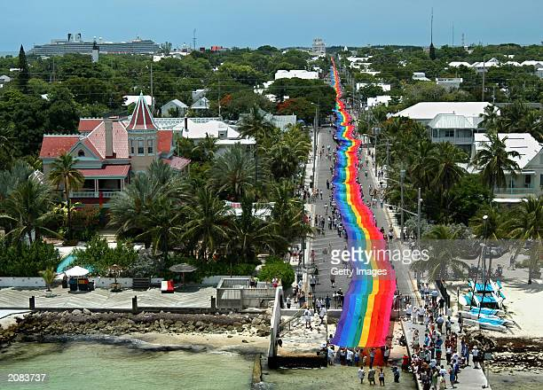 This handout photo from Florida Keys News Bureau shows volunteers helping to stretch the mile and quarter long 'World's longest Rainbow Flag' June 15...