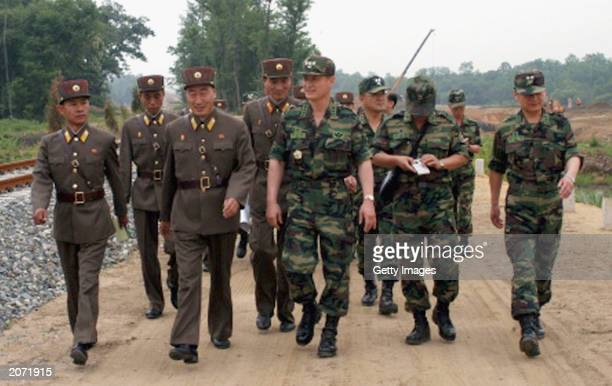 This handout photo shows South Korean military officers talking with North Korean military officers as they check the progress of construction on the...