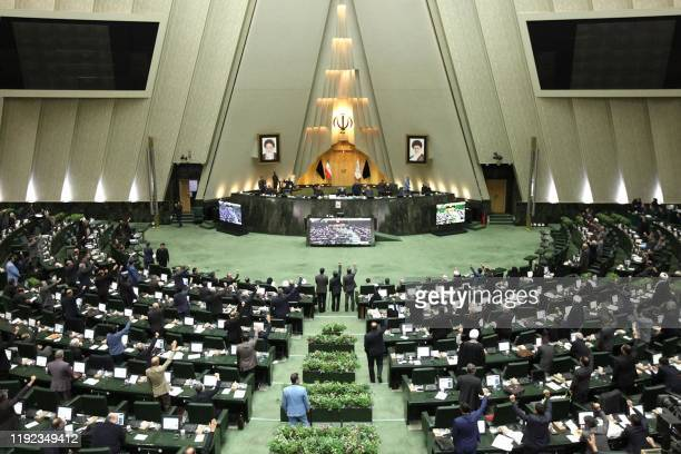 This handout picture provided by the Islamic Consultative Assembly News Agency on January 7 2020 shows Iranian lawmakers raising their hands to vote...