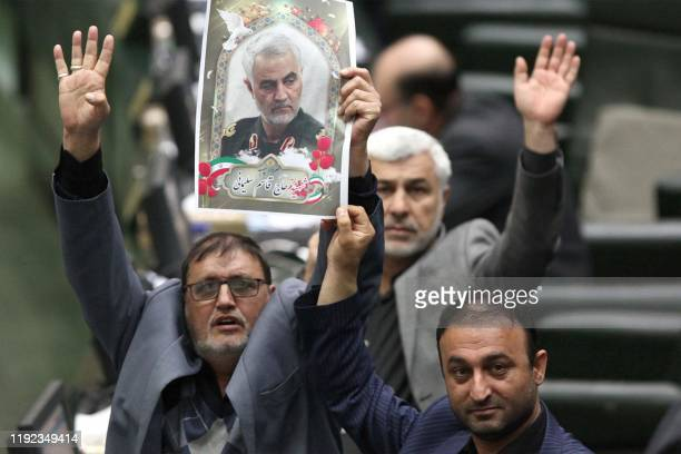 This handout picture provided by the Islamic Consultative Assembly News Agency on January 7 2020 shows Iranian lawmakers holding pictures of slain...