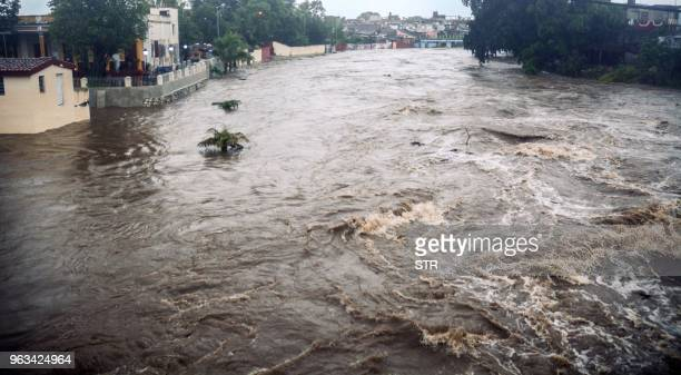 This handout picture released by the Cuban News Agency shows a river overflowing its banks due to heavy rains associated with subtropical storm...