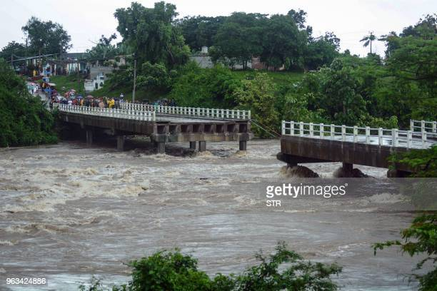 This handout picture released by the Cuban News Agency shows residents of the town of Zaza del Medio looking at a collapsed bridge caused by heavy...