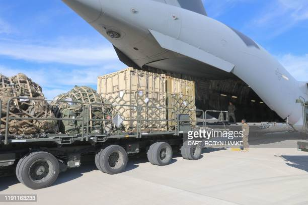 This handout picture released by the US Army shows airmen assigned to 43rd Air Mobility Operations Group conducting loading operations on C-17...