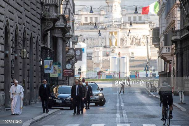 TOPSHOT This handout picture released by the Vatican Media shows Pope Francis walking in an empty Via del Corso in the Rome on March 15 2020 The...
