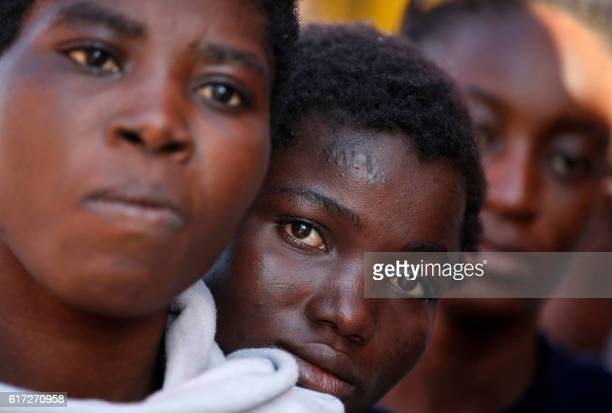 TOPSHOT This handout picture taken and released by the Italian Red Cross on October 22 2016 shows a woman looking on as migrants land in Vibo Marina...