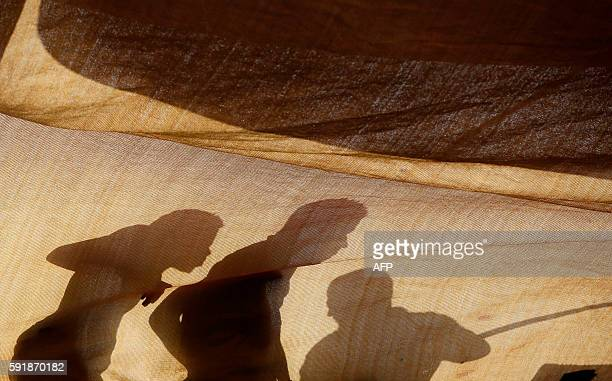 This handout picture taken and released by the Italian Red Cross shows migrants' shadows reflected on a sheet on the flagship rescue vessel MY...