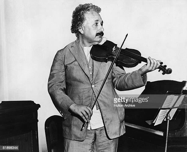 This heavily retouched photograph shows German-Swiss-American mathematical physicist Albert Einstein as he plays a violin in the music room of the...