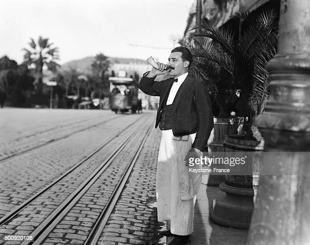 This hotel employee uses a call horn to get a taxi for customers in 1928 in Cannes France