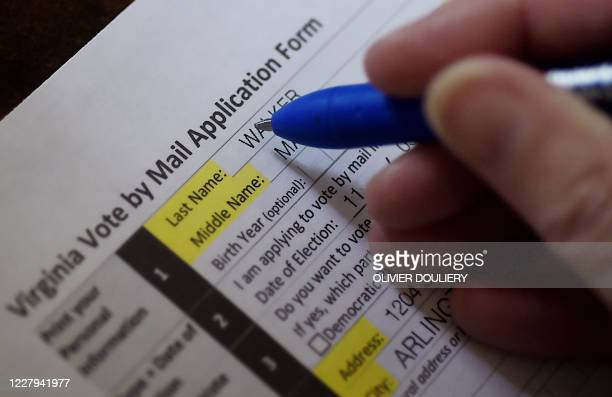This illustration photo shows a Virginia resident filling out an application to vote by mail ahead of the November Presidential election, on August...