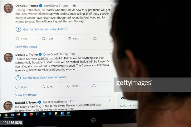 TOPSHOT This illustration photo shows an editor in Los Angeles looking at the official Twitter account of US President Donald Trump on May 26 with...