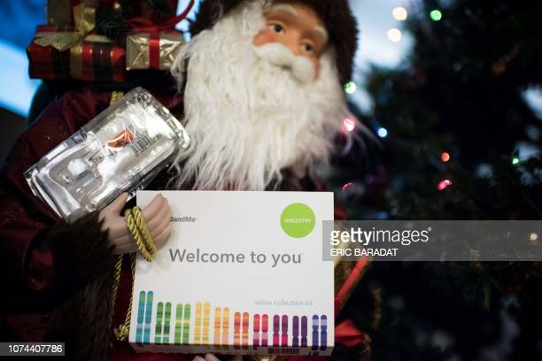 This illustration picture shows a saliva collection kit for DNA testing displayed in the arms of a Father Christmas doll in Washington DC on December...