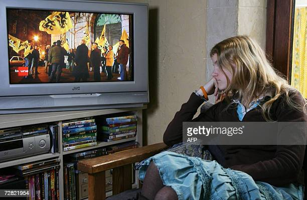 This illustration picture shows a teenager girl watching the Belgian television channel RTBF 13.00h television journal commenting the RTBF special...
