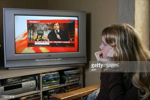 This illustration picture shows a teenager girl watching the RTBF 13.00h television journal commenting the RTBF special broadcast, fiction of...