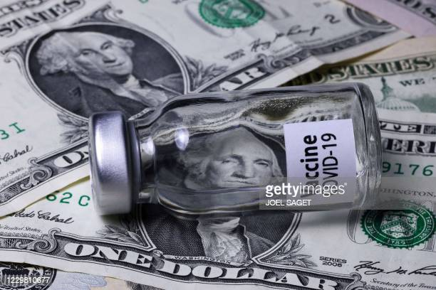 "This illustration picture shows a vial reading ""Covid-19 Vaccine"" with dollar banknotes, in Paris, on November 26, 2020 ."