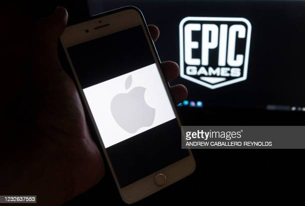 This illustration picture shows the logo from Epic Games displayed on a laptop and an Apple Logo on an iPhone in Arlington, Virginia on April 30,...