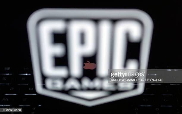 This illustration picture shows the logo from Epic Games displayed on a laptop and a reflected Apple Logo on an iPhone in Arlington, Virginia on...