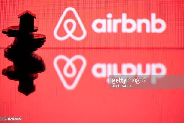 This illustration picture taken in Paris on August 29 a toy house on coins next to the logo of housing website Airbnb