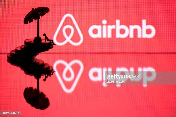 This illustration picture taken in Paris on August 29 a toy umbella and a figurine on coins next to the logo of rental website Airbnb