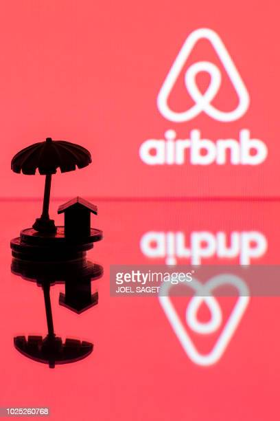 This illustration picture taken in Paris on August 29 a toy umbella and house on coins and a figurine next to the logo of rental website Airbnb