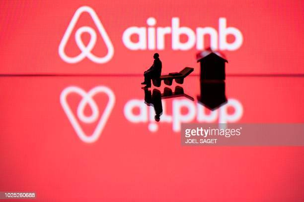 This illustration picture taken in Paris on August 29 shows a toy house and a figurine next to the logo of rental website Airbnb