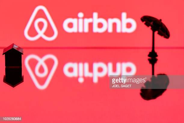 This illustration picture taken in Paris on August 29 shows a toy umbella and house next to the logo of rental website Airbnb