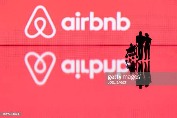 This illustration picture taken in Paris on August 29 shows figurines next to the logo of rental website Airbnb