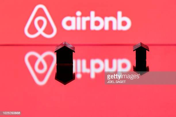 This illustration picture taken in Paris on August 29 shows toy houses next to the logo of rental website Airbnb