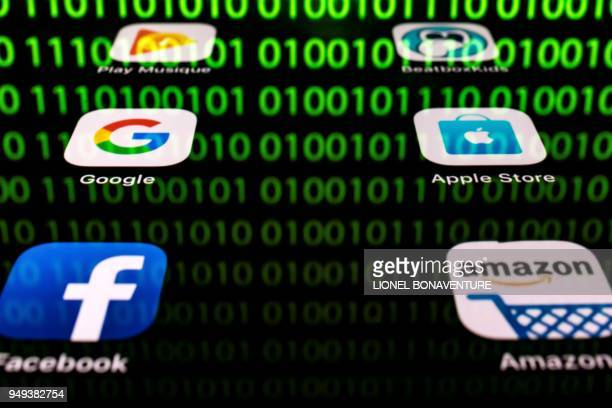 This illustration picture taken on April 20 2018 in Paris shows apps for Google Amazon Facebook Apple and the reflexion of a binary code displayed on...