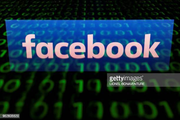 This illustration picture taken on April 29 shows the logo of social network Facebook displayed on a screen and reflected on a tablet in Paris