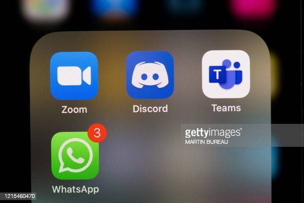 This illustration picture taken on May 27, 2020 in Paris shows the logos of the social networks applications Zoom, Discord, Teams and WhatsApp on the...