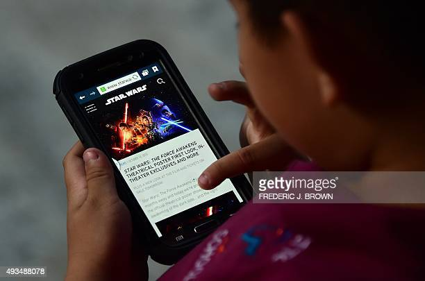 This illustration shows a child reading about the latest Star Wars film 'The Force Awakens' on a mobile phone in Los Angeles California on October 20...