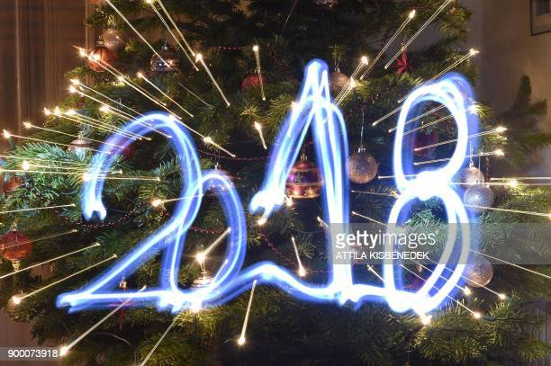 TOPSHOT This illustration taken with a long time exposure and with zoom effect on December 31 2017 in Budapest Hungary shows the year '2018' painted...