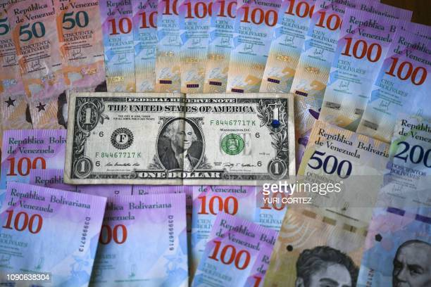 This ilustration shows Venezuelan Bolivar banknotes and a US one-dollar bill in Caracas on January 28, 2019. - Venezuela devalued its currency by...