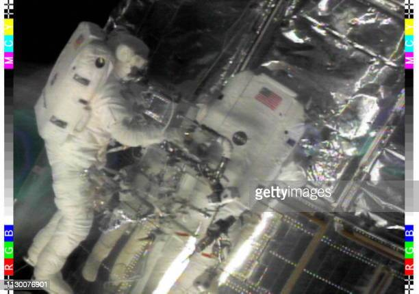 This image from NASA video shows Space Shuttle Discovery Astronaut Mark Lee late 17 February working to repair some of the Multi Layer Thermal...