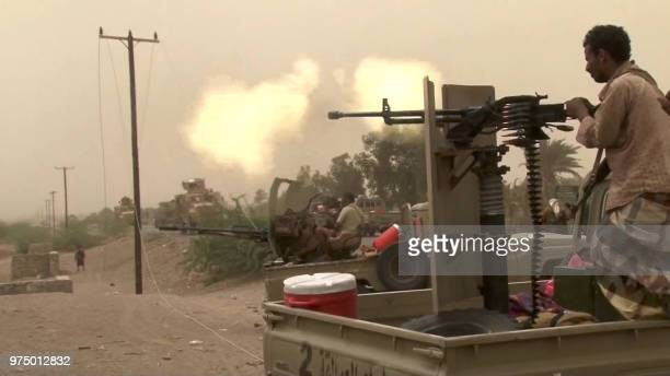 This image grab taken from a AFPTV video shows Yemeni pro-government forces firing a heavy machine gun at the south of Hodeida airport, in Yemen's...