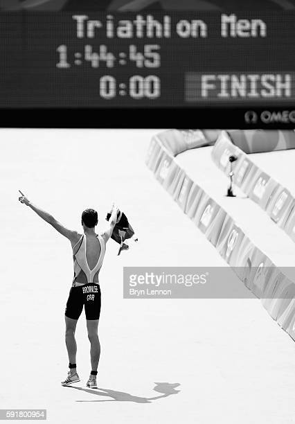 This image has been converted to black and white.] Alistair Brownlee of Great Britain celebrates after crossing the finish line during the Men's...