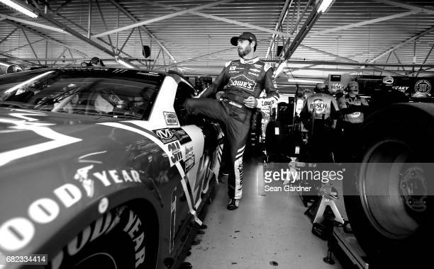 This image has been converted to black and white.] Jimmie Johnson, driver of the Lowe's Chevrolet, gets into his car during practice for the Monster...