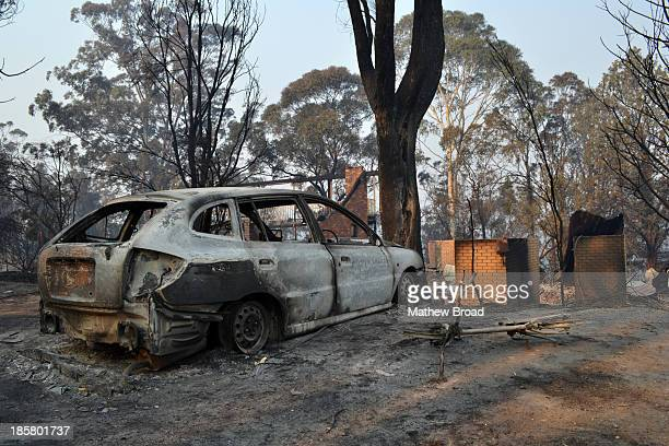 This image is from the Linksview Rd bushfire in Winmalee, Blue Mountains, Australia. October 2013. A burnt out car and kids pushbike sit in front of...