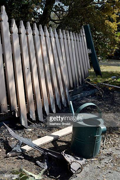 This image is from the Linksview Rd fire in Springwood, the Blue Mountains, Australia. A watering can sits next to a section of burnt picket fence...