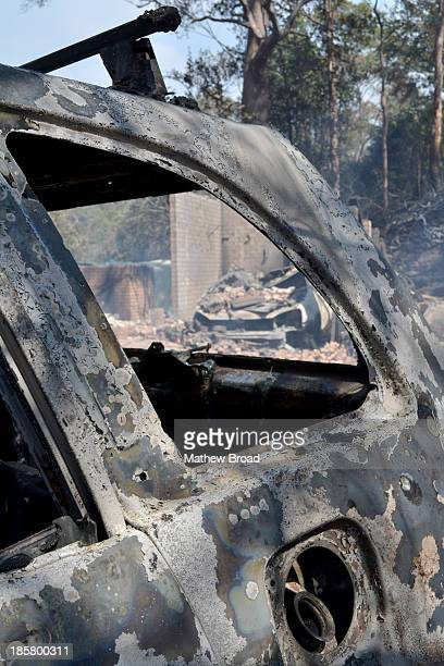 This image is from the Linksview Rd fire in Winmalee, the Blue Mountains, Australia. Two burnt out cars sit in front of a burnt out house in...