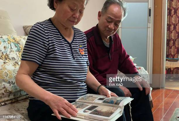 This image made from video taken on April 19 2019 shows Song Xinling and Wu Dingfu looking at photos of their son Wu Guofeng at their home in Chengdu...